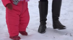 Newborn Baby Girl Walking She's First Steps in a Winter Day. 4K UltraHD, UHD Stock Footage