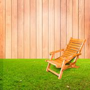 wooden deck chair on green grass with wooden wall background - stock photo