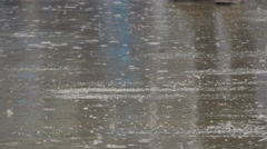Rain drops falling in puddle on street, reflection of people legs during walk. - stock footage