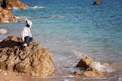 Sweet little boy, sitting on a big rock in the ocean, contemplating - stock photo