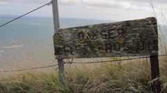 Danger Cliff Erosion Wooden Sign On Cliff Edge Ocean In Background Hand Held Stock Footage