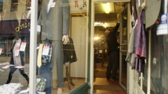 4K Shopkeepers in man's clothing store preparing the shop for the day's business Stock Footage