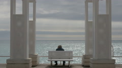 Passing by a man sitting on a white bench on Promenade des Anglais, Nice Stock Footage