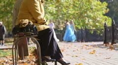 Senior women sitting on the bench in the autumn city park Stock Footage
