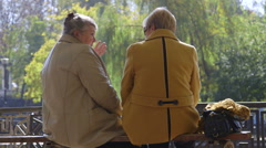 Senior women friends talking on the bench in the autumn city park - stock footage