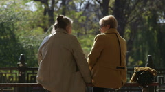 Two older women sitting on a bench talking together enjoying a sunny autumn day Stock Footage