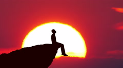 Man sit on the edge of a cliff on the background of sunrise. Real time capture Stock Footage