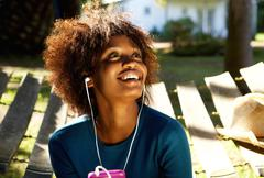 Smiling woman listening to music with cellphone and earphones Kuvituskuvat
