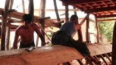 Two workers creating a boat in Myanmar by traditional old methods Stock Footage