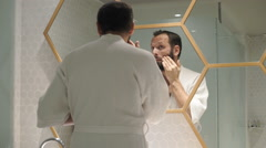 Happy man checking his appearance in mirror in bathroom  Stock Footage