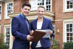 Male And Female Realtor Standing Outside Residential Property - stock photo