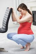Pregnant Woman Exercising Using Back Of Chair At Home Stock Photos