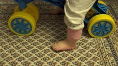 Newborn Baby Feet Next to Plastic Bicycle. Closeup. 4K UltraHD, UHD Stock Footage