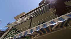 Summer hotel exterior with retractable striped awnings and spiral staircase Stock Footage