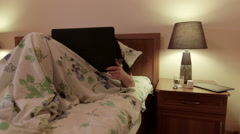 Woman lying in bed using laptop at night on bedside table sleeping pills Stock Footage