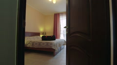 View through the open door to the hotel room with travel bag on bed Stock Footage