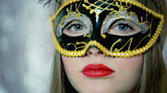 Stock Video Footage of Woman in carnival mask showing silence sign to the camera, steadycam shot