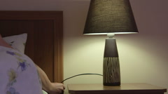 Woman in bed falling asleep turning off bedside lamp at night Stock Footage