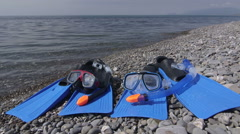 Two wet snorkeling sets fins scuba masks on wild pebble beach in summer Stock Footage