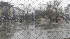 Chain-link fence, downpour and sport court, people with umbrellas in background. Stock Footage