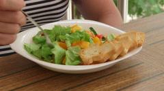 Woman having outside light lunch on the balcony eating fresh vegetable salad Arkistovideo