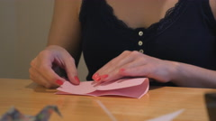 Girl Folding Crane Origami using pink paper - stock footage