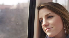 Young woman on a train listens to music in her headphones and smiles Stock Footage