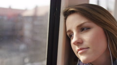 Young woman on a train listens to music in her earphones smiling, in slow motion Stock Footage