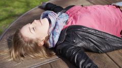 Young woman laying on a merry go round as it spins, in slow motion Stock Footage