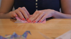Girl Folding a Red Crane Origami Stock Footage