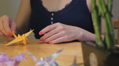 Girl Folding a Yellow Crane Origami Stock Footage