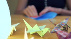 Girl Folding Blue Crane Origami - stock footage