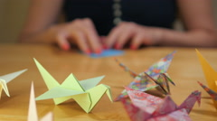 Panning shot of a Girl Hands Folding Crane Origami Stock Footage