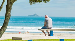 Middle Aged Man Sitting on Bench at Main Beach Tauranga Stock Footage