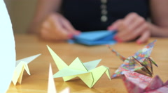 Panning shot of a Girl Hands Folding Crane Origami - stock footage