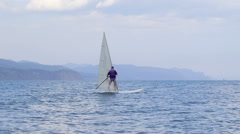 Man getting windsurfing lessons along shoreline in a sea Stock Footage
