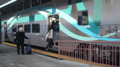 Cargo cart passes by as the passenger gets onto amtrak metrolink train - stock footage