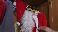 Man opening the closet door and pulling out Santa Claus suit costume - stock footage