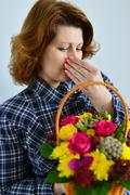 Woman with allergic rhinitis is holding a bouquet of flowers Stock Photos