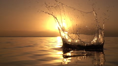 SLOW MOTION CLOSE UP: Throwing rock into ocean at sunset - stock footage