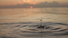 SLOW MOTION CLOSE UP: Water drop falls into ocean surface Stock Footage