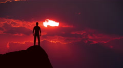 Man stand on the head of mountain against the red background of sunset Stock Footage