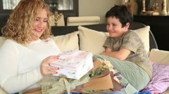 Cute boy offering gift to her mother in the living room  - stock footage