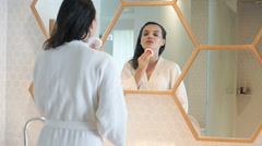 Young woman in bathrobe cleaning her face with cotton pad in bathroom  Stock Footage