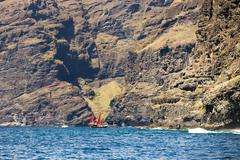 Sailing ship with red sails in front of the cliffs at Los Gigantes Santiago del Stock Photos