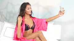 Sexy ethnic lingerie girl taking selfies on bed - self portrait Stock Footage