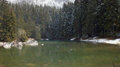 Clear Mountain Pond with Snowfall - stock footage