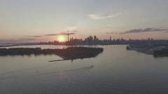 Aerial shot city landscape camera following a boat during sunset long range - stock footage
