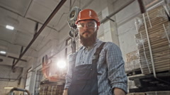 Bearded industrial worker in protective helmet and goggles at the steel timber Stock Footage