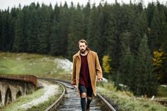brutal bearded man walks on the tracks - stock photo